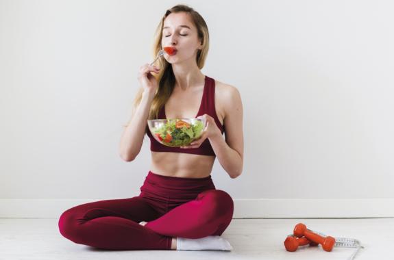 donna che mangia l'insalata in una ciotola mentre fa sport